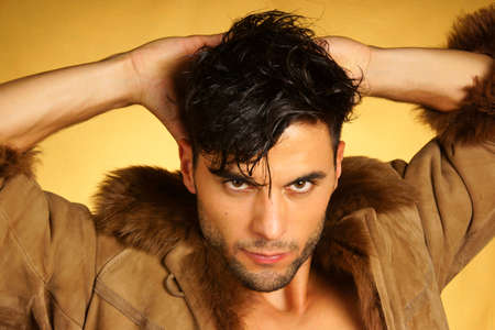 30 year old: Portrait of a 30 year old caucasian man wearing a brown leather jacket with fur over a yellow background.