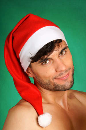 30 year old: Portrait of a sexy smiling 30 year old young man wearing Santa Claus hat over green background.