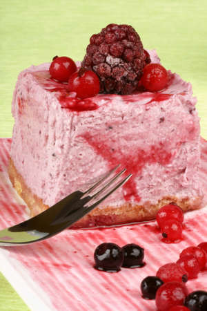 wildberry: Wild berries bavarian cream (Bavarian) on a white dish with dessert fork over a green background. Stock Photo