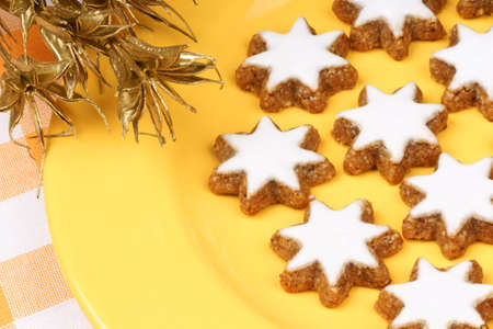 german swiss: Cinnamon star cookies (in german Zimtsterne) are typical german and swiss Christmas cookies made of almonds. Over a yellow plate.