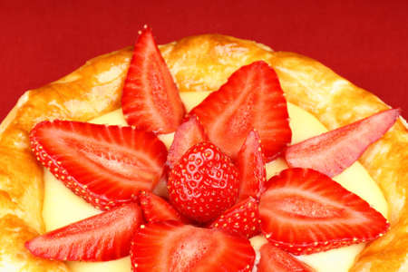 Close-up of a strawberry and custard tart a red background. photo