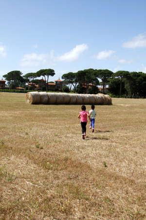 to hasten: two little girls in the area to hasten the haystack Stock Photo