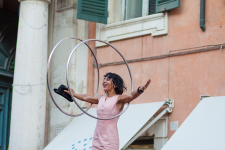 busker: FERRARA, Italy - August 29, 2015: Buskers Festival 2015 in Ferrara, Emilia Romagna, Italy. Busker Festival is a popular event with street artists which is held annually in the historic center of Ferrara.In the picture La Tanik Hula Hoops Editorial
