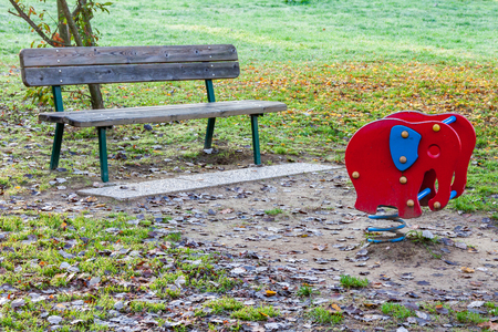 bench alone: a wooden bench alone among fallen leaves Stock Photo