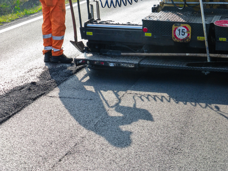 resurfacing: Workers spread asphalt on a hot summer day