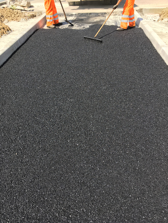 resurfacing: manual asphalting of a road in summer