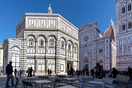 Florence, Italy - February 25, 2017: Baptistery (Battistero di San Giovanni, Baptistery of Saint John) on Piazza del Duomo, with the cathedral bell tower