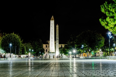 Istanbul, Turkey- September 20, 2017: Obelisk of Theodosius in the ancient Hippodrome Square in Istanbul, view at night with people sitting on benches