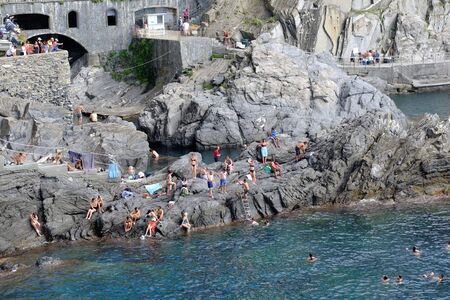Manarola, Italy- September 17, 2018: Bathers in the Ligurian sea of the ancient and typical Cinque Terre village in summer