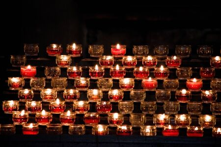 red candles in glass jars lit in a dark church Stock fotó
