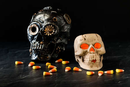 Close up front view of two spooky skulls surrounded by candy corn for Halloween. Stok Fotoğraf - 130721771
