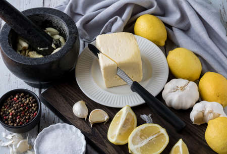 Top down view of various ingredients commonly used in gourmet cooking such as butter, garlic, lemons, salt and peppercorns.