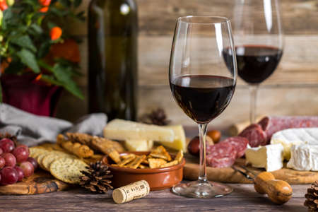 Close up view of an arrangement of wine, cheese and crackers for a party.