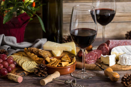 Close up view of two wine glasses with red wine surrounded by an arrangement of cheese, crackers and salami ready for snacking. Banco de Imagens