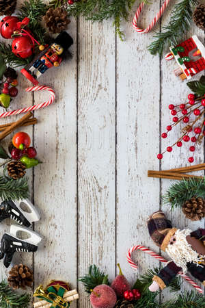 A flat lay view of an arrangement of Christmas decorations and pine branches with copy space in the middle.