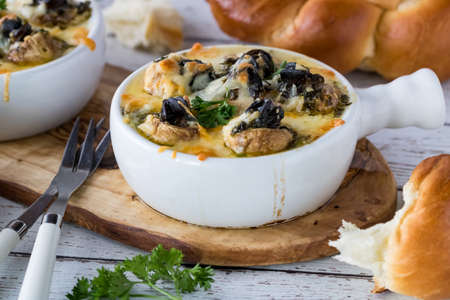 Close up view of a dish with escargot stuffed mushroom caps topped with melted cheese and hot garlic butter ready for eating. Banco de Imagens - 133166276