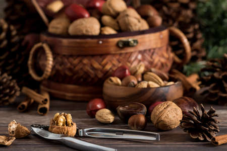 Front view of a basket of mixed nuts with a small bowl of nuts in front and a nut cracker with a cracked open walnut.