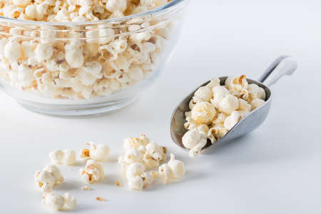 A close up front view of a metal scoop filled with popcorn and a glass bowl of the same in behind.
