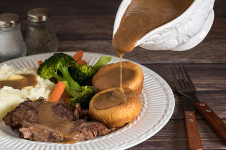 Close up view of a plate of roast beef, yorkshire pudding, mashed potatoes and gravy with gravy being poured into the yorkshire pudding. Stock fotó