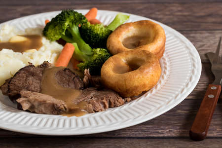 Close up view of a plate of roast beef, yorkshire pudding, mashed potatoes and gravy ready for eating.