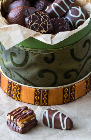 A close up view of a fancy round box filled with decorated chocolates with two chocolates on parchment paper in front.
