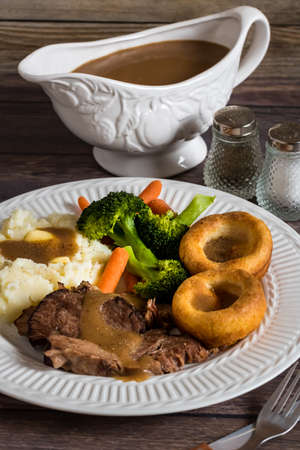 Close up view of a plate of roast beef, yorkshire pudding, mashed potatoes and gravy with a gravy boat in behind. Stock fotó