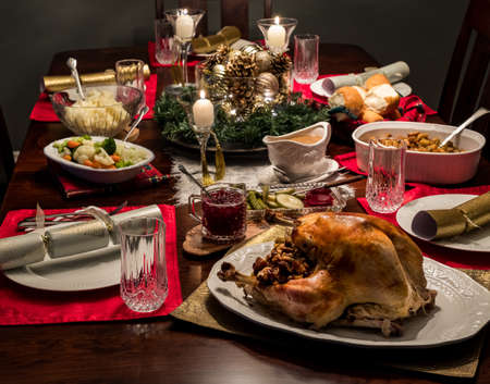 Close up of a Christmas dinner table complete with turkey and all the fixings including gravy and cranberry sauce. Stockfoto