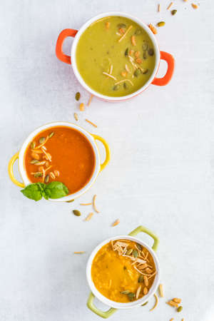 Top down view of three bowls of different kinds of hot soup ready for eating. Copy space to the right. Stock Photo