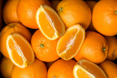A top down view of a case of fresh navel oranges with an orange cut into quarters on top.