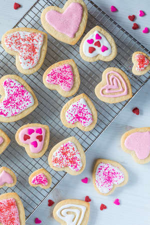 A top down view of a variety of decorated heart shaped sugar cookies on a cooking rack for Valentine's Day.