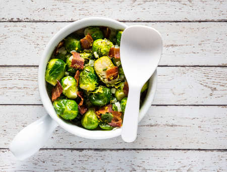 A top down view of a casserole dish filled with cooked brussel sprouts mixed with bacon and cream sauce with a white spatula for serving.