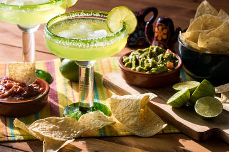 Close up view of glasses filled with lime margarita cocktails surrounded by nacho chips, guacamole and salsa.