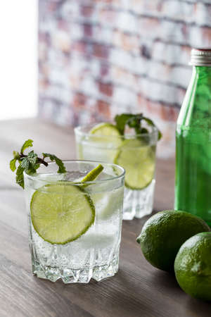 A glass of sparkling water with lime slices and mint on a wooden table against a sunny window and brick wall.