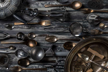 Top down view of an abstract arrangement of antique utensils and cutlery against a dark background.