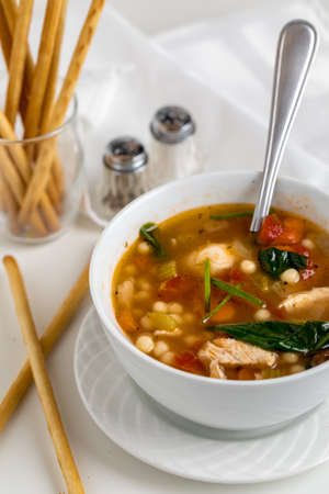 A top down close up view of a bowl of homemade chicken vegetable with Israeli couscous soup served with breadsticks.
