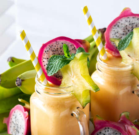 Close up of two glass jars of tropical exotic fruit smoothies ready for drinking.