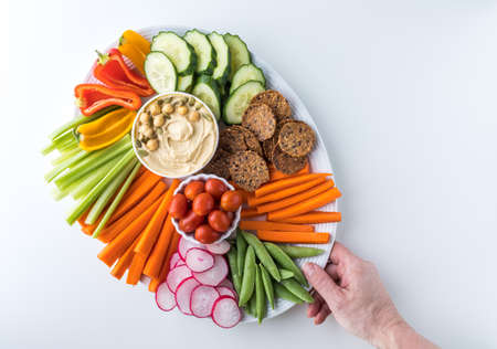 A top down view of a platter filled with crudites and a small bowl of hummus.
