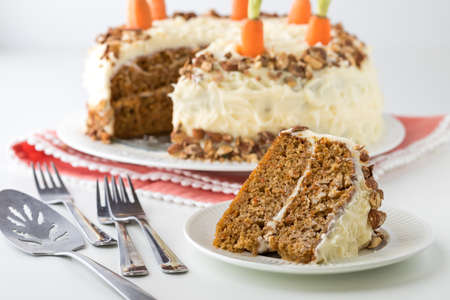 Close up of a carrot cake with cream cheese frosting and a piece of cake in front ready for eating. Imagens