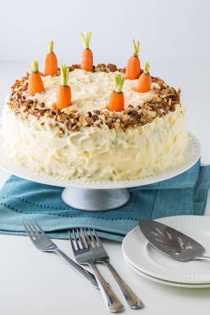 A close up of a whole carrot cake with cream cheese frosting and serving dishes in front.