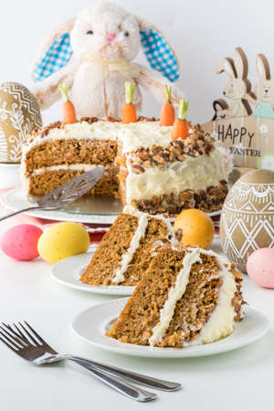 A close up of two pieces of carrot cake with the cake in behind and surrounded by Easter decorations.