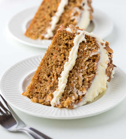 Close up view of two pieces of carrot cake with cream cheese frosting ready for eating.