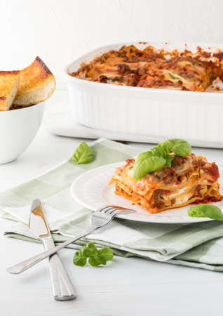 Close up of a slice of lasagna with the pan of lasagna in behind and a dish of garlic toast.