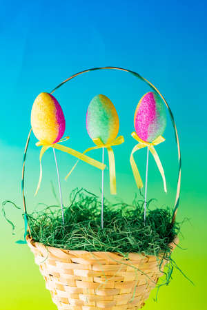 Close up of a woven Easter basket filled with grass and decorated Easter eggs against a colourful background.