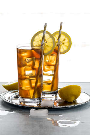 Two backlit glasses of frosty ice tea with lemon slices ready for drinking.