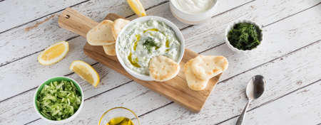 A top down cropped view of a bowl of tzatziki dip with pita bites ready for snacking.