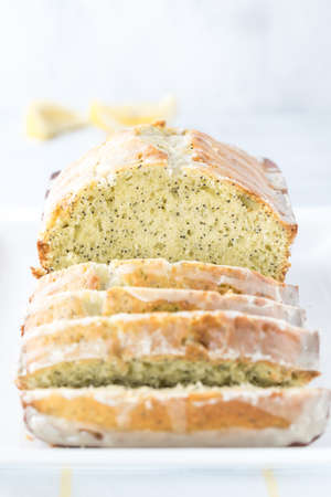 A close up front facing view of a lemon poppy seed loaf sliced into and ready for eating.