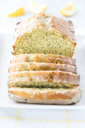 A front facing close up view of a lemon poppy seed loaf that has been sliced into.