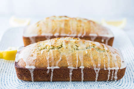 Close up of two glazed lemon poppy seed loaves on a tray.