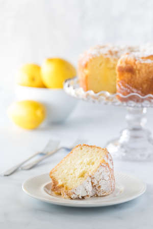 Front view of a slice of lemon bundt cake with the cake on a cake stand, forks and a bowl of lemons in soft focus. Stock Photo