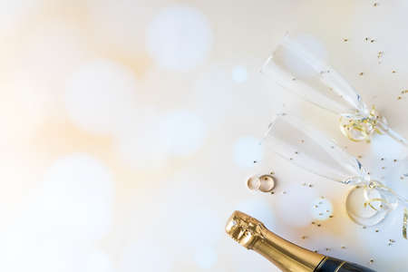 A top down view of champagne flutes and bottle as well as wedding rings, against a bokeh background and glitter. Standard-Bild